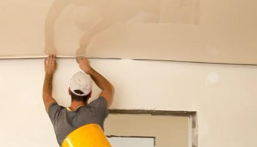 Работник занят монтажом натяжного потолка